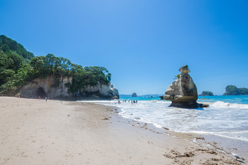 Cathedral Cove in Coromandel Peninsula on the North Island of New Zealand. People can seen exploring around it.