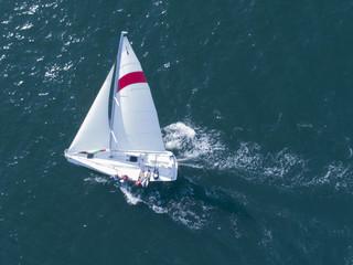 帆に風を受け進むヨットでくつろぐ人達