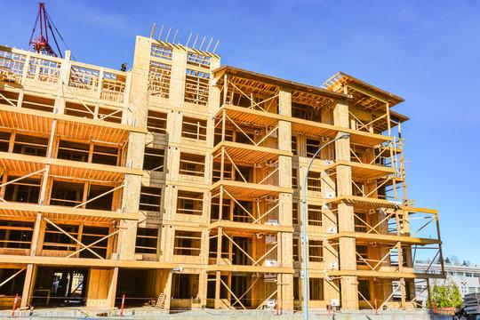 Six storey frame building under construction on concrete foundation bed on blue sky background