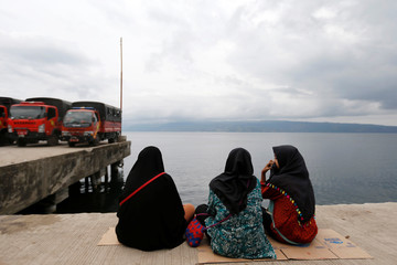 Relatives of the missing passengers from a ferry accident at Lake Toba sit on a pier in Simalungun