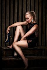 Beautiful sexy blonde woman in short black dress