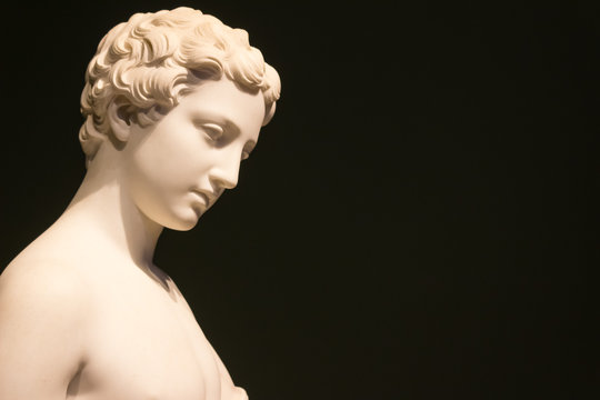 Marble statue of a woman with short hair with bare shoulders with a black background.