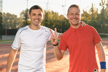Two men practicing sport in the morning showing victory sign
