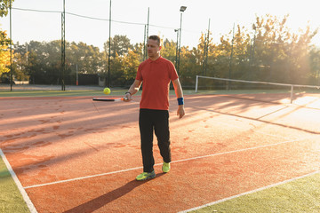 Athletic man warming up hitting the ball with racket