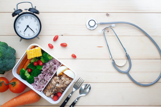 Creative flat lay of nutrition food in lunch box with chicken breast, boiled egg, rice and vegetables. Healthcare and healthy food with stethoscope