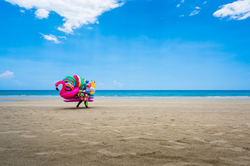 A dealer in inflatable swimming circles walks along the beach