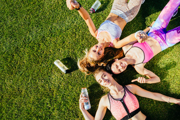 Top view portrait of a three happy positive sporty women in sportswear resting on grass and waving at camera after workout. Friendship, healthy lifestyle concept. Copy space.