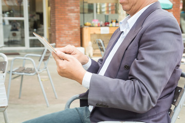 Asian Businessman in Suit use Digital Wireless Tablet outdoor in Public