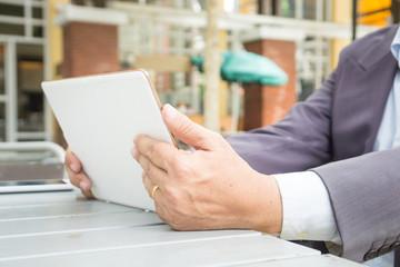 Asian Businessman in Suit use Digital Wireless Tablet outdoor in Public