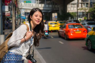 woman on the road looking for taxi