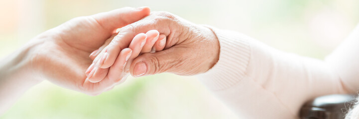 Close-up of tender gesture between two generations. Young woman holding hands with a senior lady. Blurred background. Panorama. Wall mural