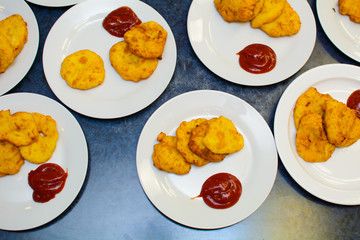 many servings of potato pancakes with ketchup on plates