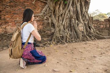 female backpacker kneeling down beside to the tree