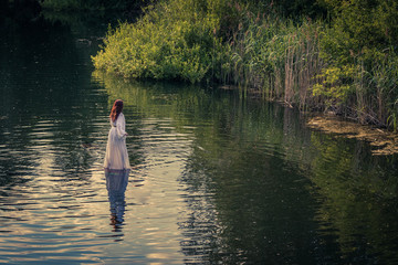 Red long hair Nymph woman in a white dress walking on the water surrounded by reeds trees and grasses