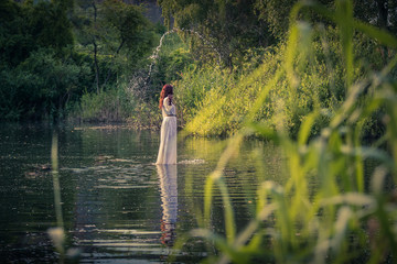 Red long hair Nymph woman in a white dress holding a chalice and spreading drops standing on the water surrounded by reeds trees and grasses in sunlight