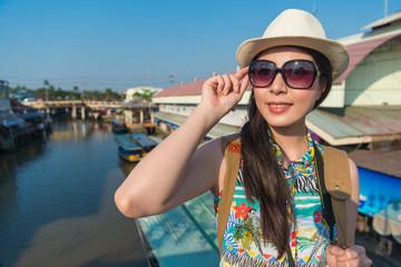 woman look at camera and lift glasses on bridge
