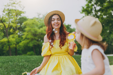 Smiling woman in yellow dress play in park, have fun and amuse with little cute child baby girl hold soap bubble blower. Mother, little kid daughter. Mother's Day, love family, parenthood, childhood.