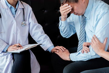 Patient listening intently to a male doctor explaining patient symptoms or asking a question as they discuss paperwork together in a consultation ..