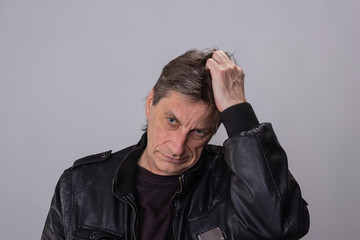 depression old adult tired a 55-year  man dressed in a black leather jacket