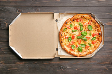 Carton box with delicious pizza Margherita on wooden background