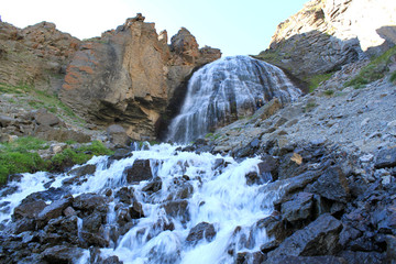 waterfall girlish braids or Carabasi-su, in Kabardino-Balkaria, near mount Elbrus, view from below a waterfall flowing through rocks and mountains with stones and green grass