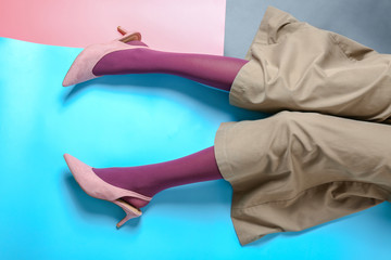 Legs of young woman in tights and trousers on color background