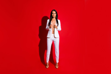 Full body portrait of playful tempting girl taking off jacket looking at camera isolated on bright red background