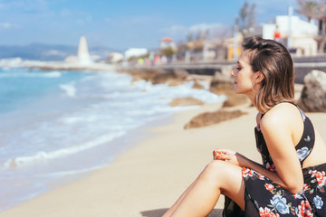 Young woman sitting on a sunny sandy beach