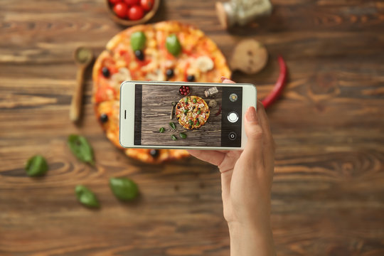 Woman taking photo of delicious Italian pizza with mobile phone