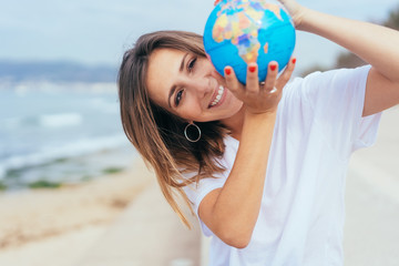 Happy excited woman holding up a world globe