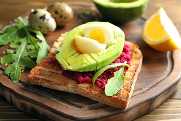 Board with tasty toast on wooden background, closeup