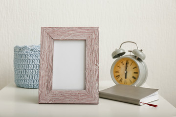 Photo frame with alarm clock and notebook on table against light background