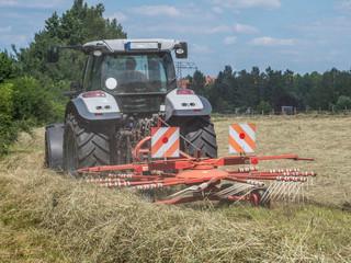 Traktor beim Heuwenden auf einem Feld