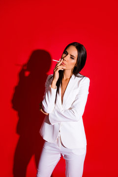 Vertical portrait of stressed disappointed woman smoking cigarette wearing white elegant suit isolated on bright red background