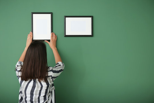 Woman hanging picture frame on color wall