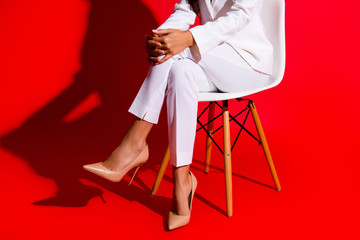 Cropped portrait of woman's legs in elegant classic white pants wearing stilettos isolated on vivid red background