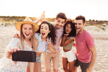 Photo of smiling young multiracial men and women 20s in summer clothes taking selfie on smartphone, while standing on sand