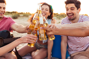Group of young and beautiful people 20s in summer clothes hanging out together, and drinking beer at beach party