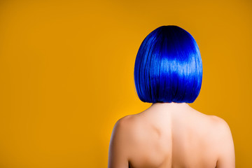 Portrait with copy space empty place for product, rear view of woman in vivid blue wig with modern hairdo isolated on yellow background