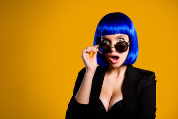 Portrait with copyspace empty place of afraid scared girl looking out glasses with big eyes wide open mouth in bright blue wig isolated on yellow background