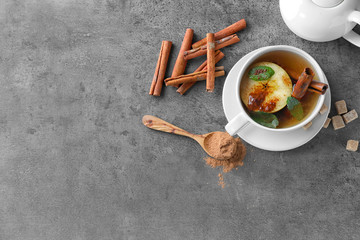 Hot drink with cinnamon sticks and apple in cup on grey background