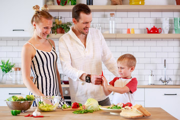 Image of young mother, father and little son preparing food in kitchen