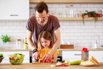 Image of father with little daughter cooking lunch