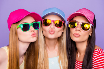 Head shot portrait of lovely sweet trio, blonde brunette ginger sending kiss with pout lips at camera isolated on vivid violet background