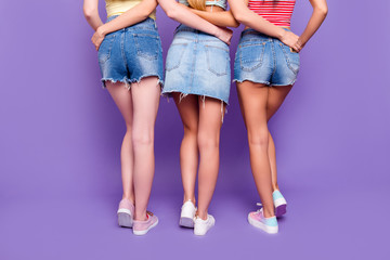 Rear view cropped portrait of lesbians trio hugging having booty butt demonstrate hairless ideal legs isolated on vivid violet background. Pampering weightloss diet weight loss concept