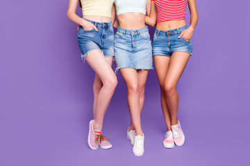 Hair removal waxed beauty wellness wellbeing concept. Cropped portrait of lesbian trio embracing demonstrate smooth ideal skin of legs isolated on bright violet background