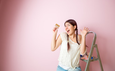 Photo of cheerful woman with brush next to stepladder and roller against blank pink wall.