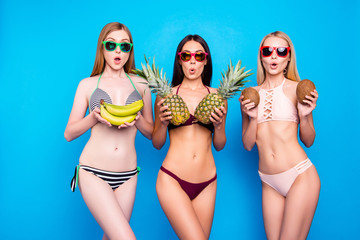 Wall Mural - Figure shape slim belly tummy fit fitness healthy lifestyle diet food nutrition concept. Portrait of frustrated trio with open mouth holding fresh fruits in hands isolated on vivid blue background