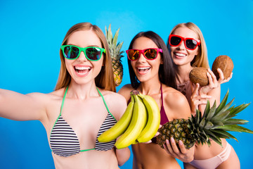 Joy pleasure mood inspiration recreation vacation concept. Self portrait of funky positive trio holding fresh fruits in hands having online meeting isolated on bright blue background