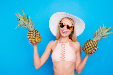 Portrait of cheerful pretty girl in pink bra summer eye glasses holding two fresh pineapples in hands looking at camera isolated on bright blue background